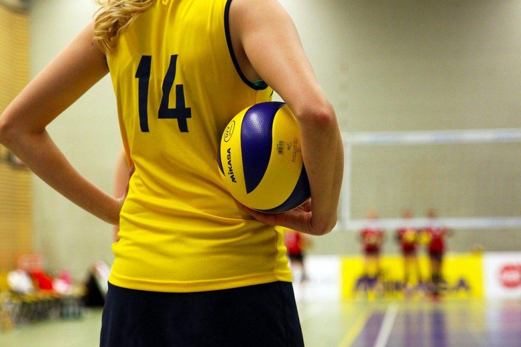 Joueuse de volley tenant un ballon face à un terrain