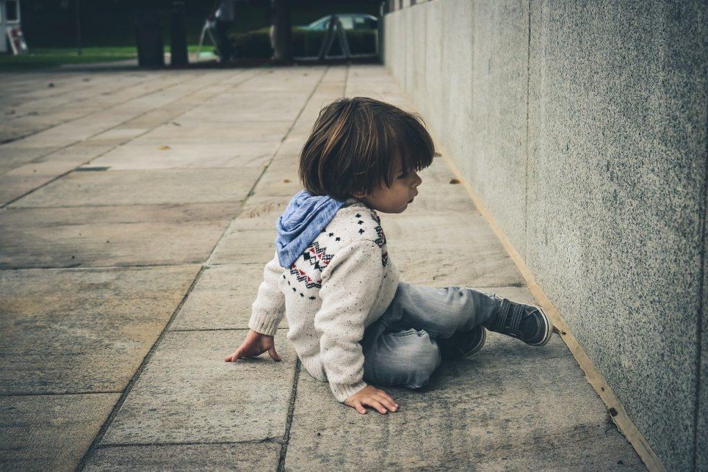 Petit garçon assis face à un mur