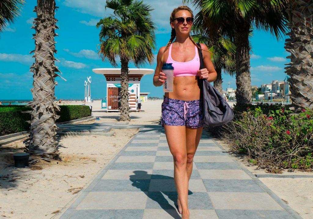 Femme sportive marchant sur un chemin en tenu et sac de sport