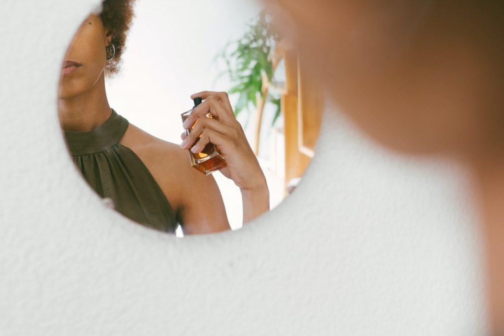 Femme se parfumant devant un miroir rond