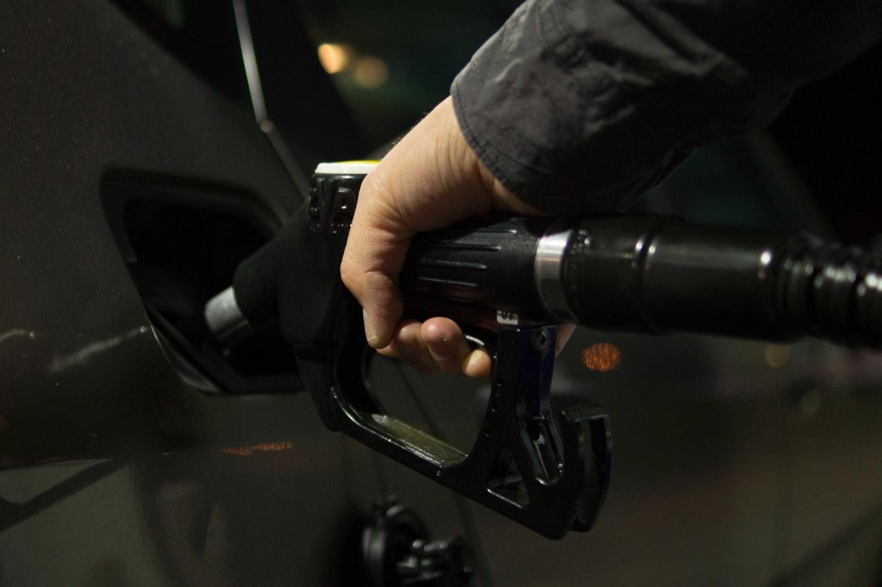 Personne tenant une pompe dans sa main et mettant du carburant dans sa voiture