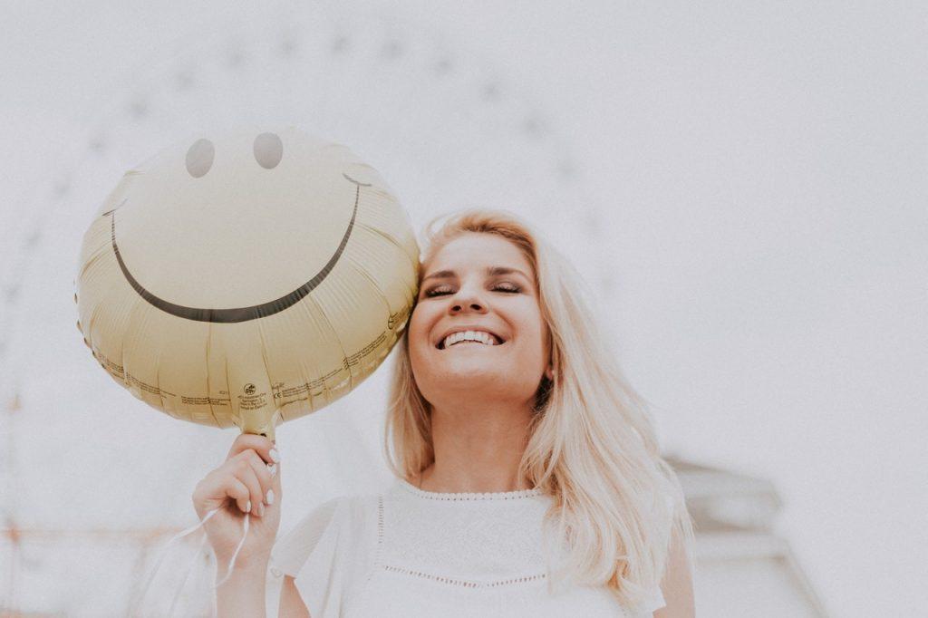 Femme blonde heureuse et souriante tenant un ballon smiley