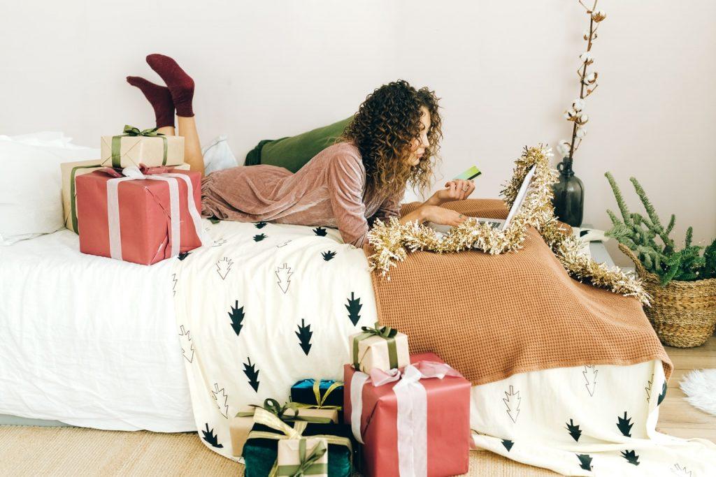 Femme faisant son shopping allongé sur son lit