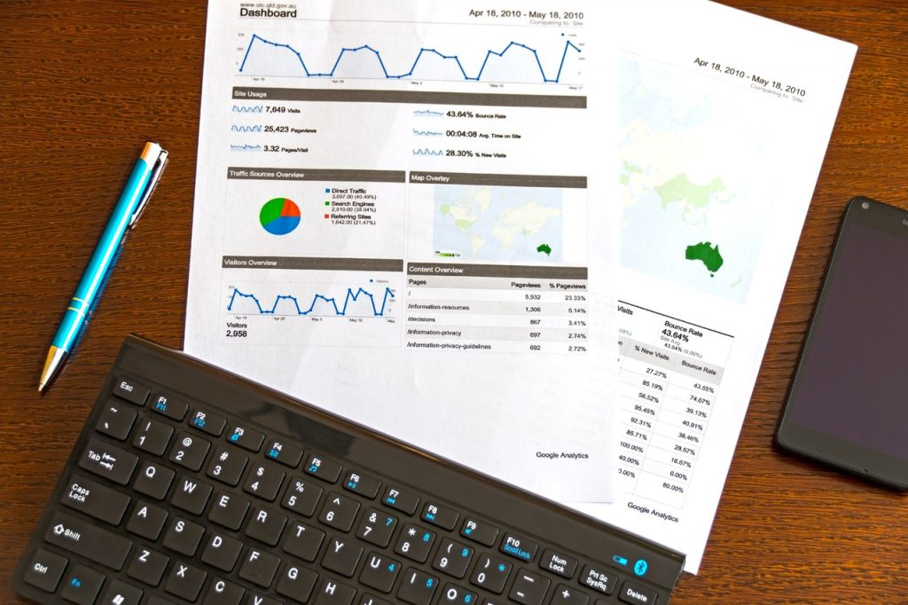 Feuilles comportant des graphiques, données statistiques, posées vers claviers