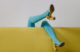 Femme tête en bas sur un canapé portant des sandales à talon et un collant bleu