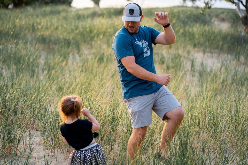 Un papa et une petite fille jouant dansant en extérieur