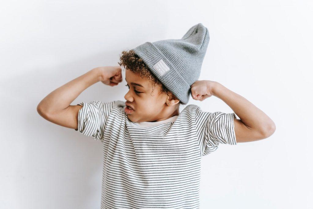 Petit garçon montrant ses muscles, pour montrer sa force