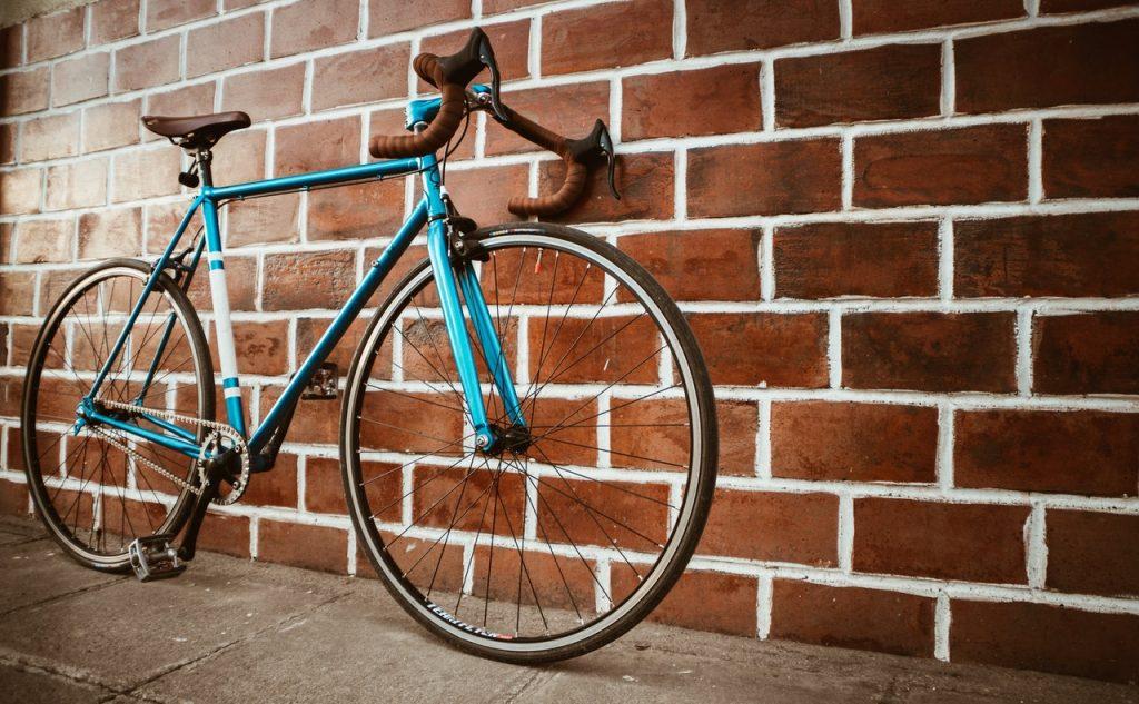 Vélo de course bleu posé contre un mur en brique