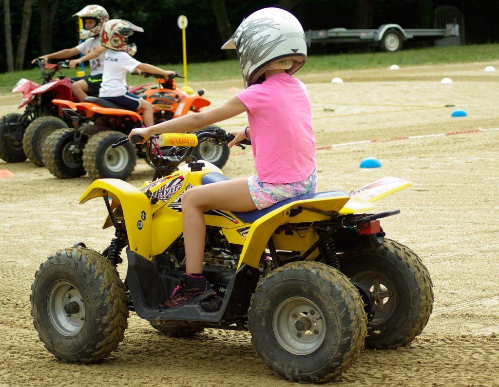 Petite fllle sur un quad enfant portant un casque