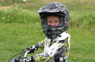 Petit garçon faisant de la moto avec un casque et une tenue de sécurité