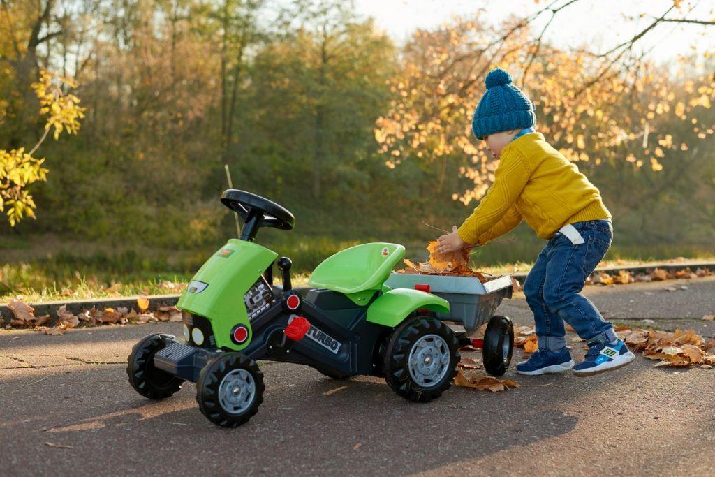 Petit garçon poussant son tracteur à pédale
