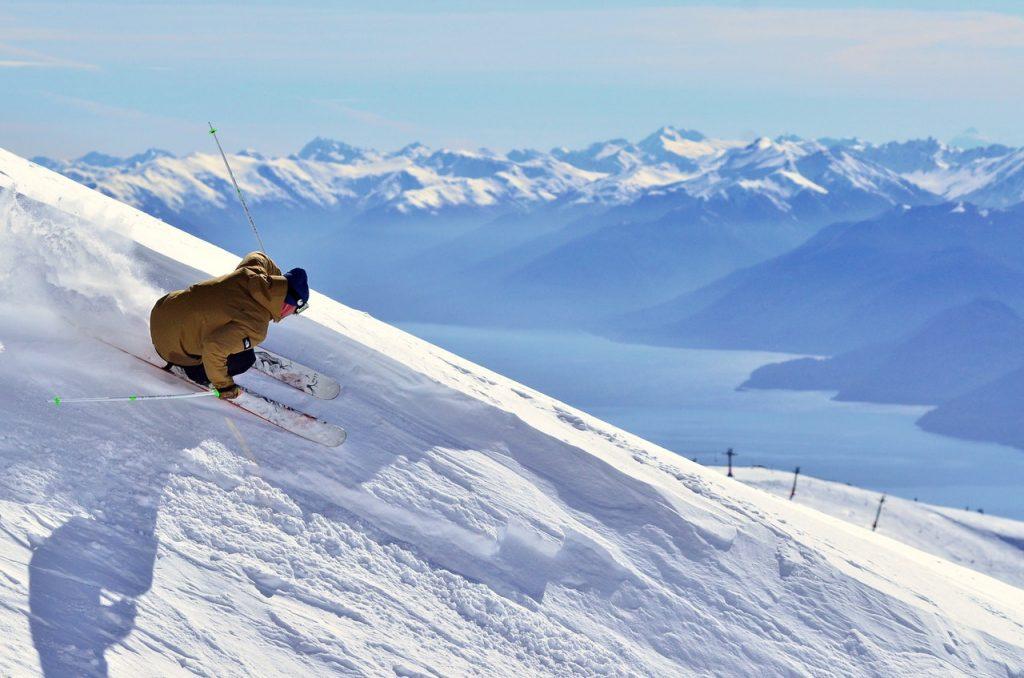 Skieur descendant piste, montagne enneigée